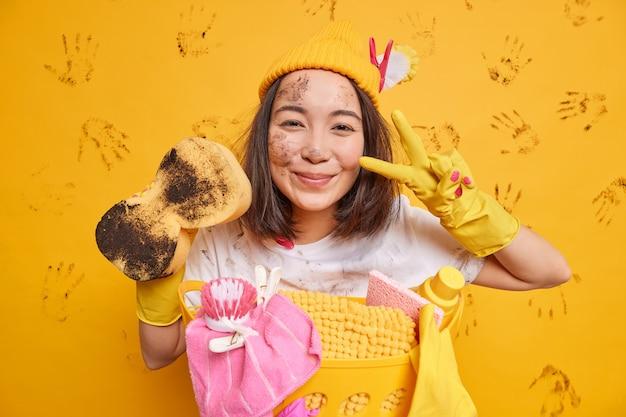 Blije aziatische huisvrouw maakt vredesgebaar draagt beschermende rubberen handschoenen houdt modderige spons vast, vuil doet de was die bezig is met regelmatig opruimen, wast alles.