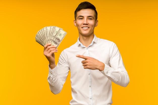 Blije aziatische man in een wit overhemd wijst naar gelddollars