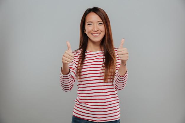 Blije aziatische vrouw die duimen met twee handen toont