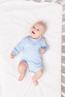 Blije baby ligt in de wieg, schattige kleine jongen van zes maanden ligt in de kinderkamer op het bed