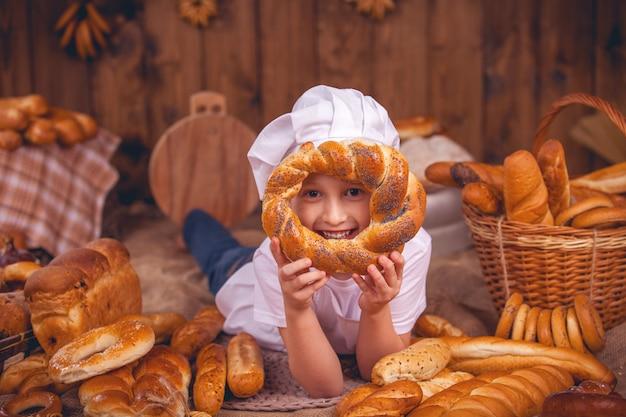 Blije babychef is een bakker die veel broodjes draagt