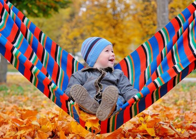 Blije babyjongen in de herfstpark op een hangmat