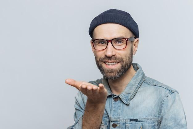 Blije bebaarde man in trendy bril drukt zijn liefde uit, toont luchtkus, heeft een vrolijke uitdrukking