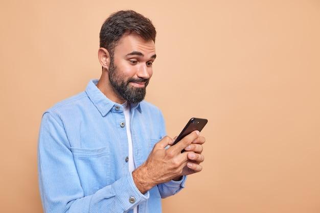 Blije bebaarde man lacht vrolijk tijdens het lezen van het bericht ontvangen op smartphone