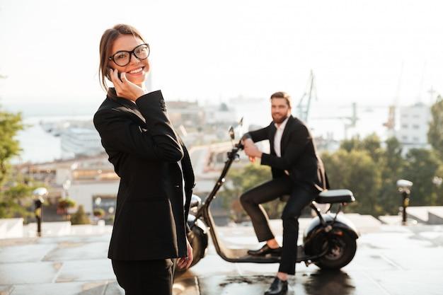 Blije bedrijfsvrouw die in openlucht stelt en telefonisch spreekt