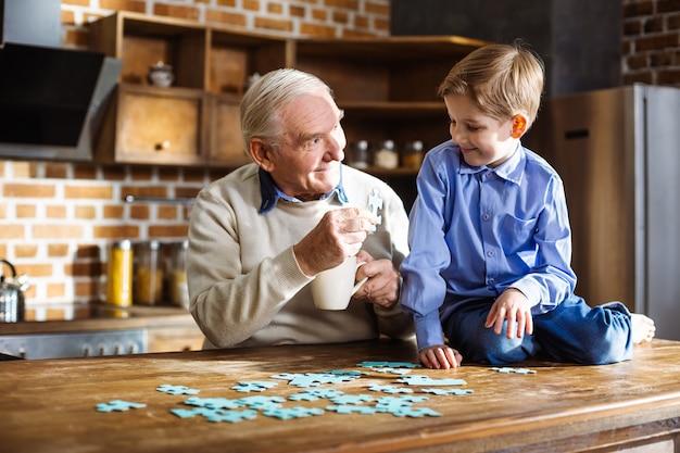 Blije bejaarde die en puzzel met zijn kleine kleinzoon glimlacht assembleert