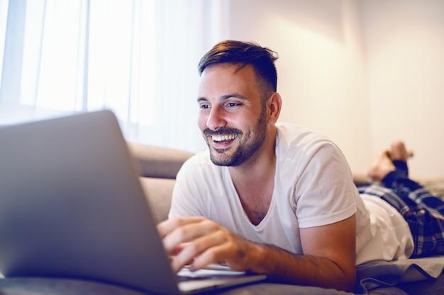Blije blanke man in pyjama liggend op de buik op de sofa in de woonkamer en surfen op internet.
