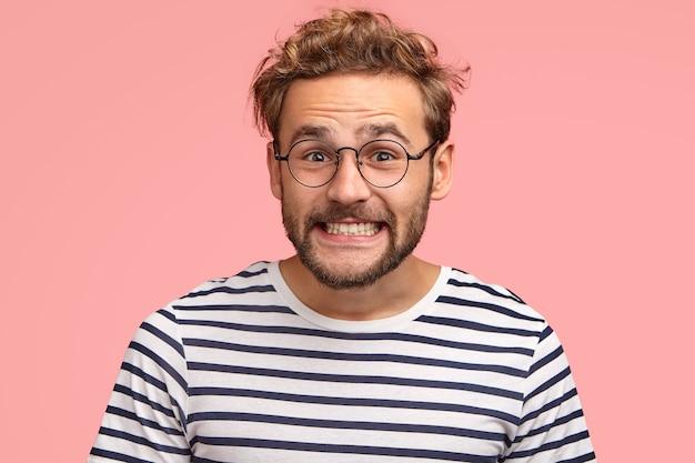 Blije blanke man klemt zijn tanden en ziet er positief uit, heeft krullend haar, draagt een bril en een gestreepte trui, geïsoleerd over roze muur. gelukkig man freelancer verheugt zich over succes