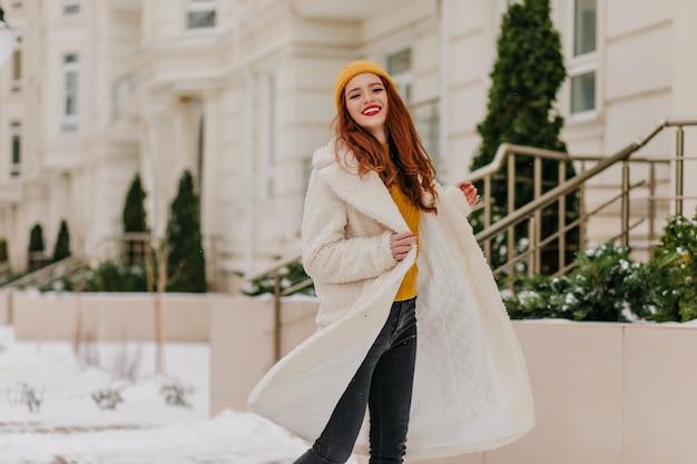 Blije blanke vrouw die in koude ochtend danst. buitenfoto van onbezorgd gembermeisje dat van de winterdagen geniet.