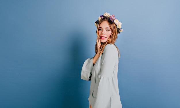 Blije blanke vrouw met mooie bloemen in haar poseren op blauwe muur