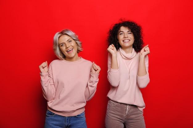 Blije blanke zusters met krullend haar poseren vrolijk op een rode achtergrond, wachtend op een cadeau