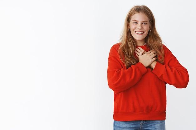Blije, blije jonge vrouw met rood haar, sproeten en blauwe ogen die vrolijk lacht met witte tanden die de handpalmen naar het hart drukt, smeltend van positieve complimenten, dankbaar over grijze muur