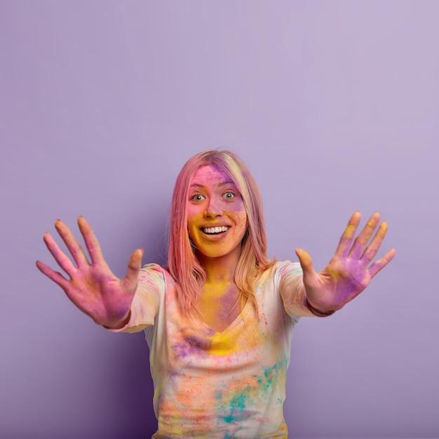 Blije blije vrouw met blond haar strekt haar handen uit en toont kleurrijke palmen vooraan, glimlacht zachtjes, tevreden na de viering van color fest in india, geïsoleerd over violette muur
