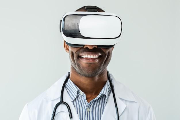 Blije blik. portret van positieve afro-amerikaanse arts die vr-bril draagt terwijl hij tegen de achtergrond staat
