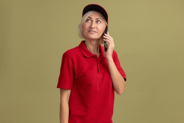 Blije blonde bezorger van middelbare leeftijd in rood uniform en pet die aan de telefoon praat en omhoog kijkt