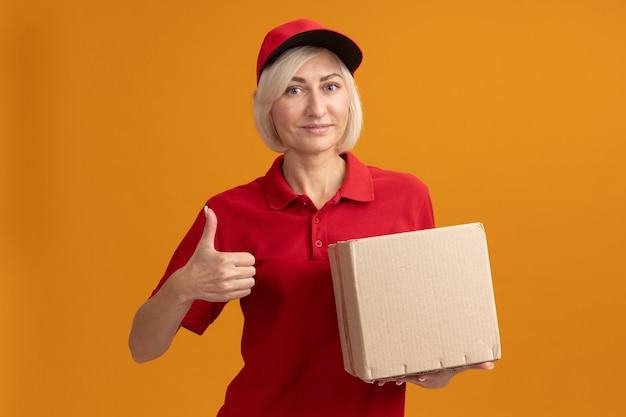 Blije blonde bezorger van middelbare leeftijd in rood uniform en pet met kartonnen doos die naar de voorkant kijkt en duim omhoog laat zien geïsoleerd op oranje muur