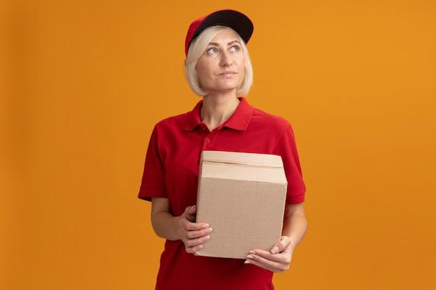 Blije blonde bezorger van middelbare leeftijd in rood uniform en pet met kartonnen doos die omhoog kijkt