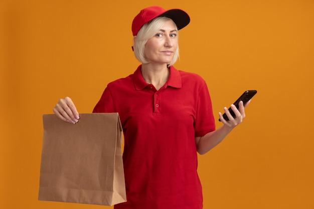 Blije blonde bezorger van middelbare leeftijd in rood uniform en pet met papieren pakket en mobiele telefoon