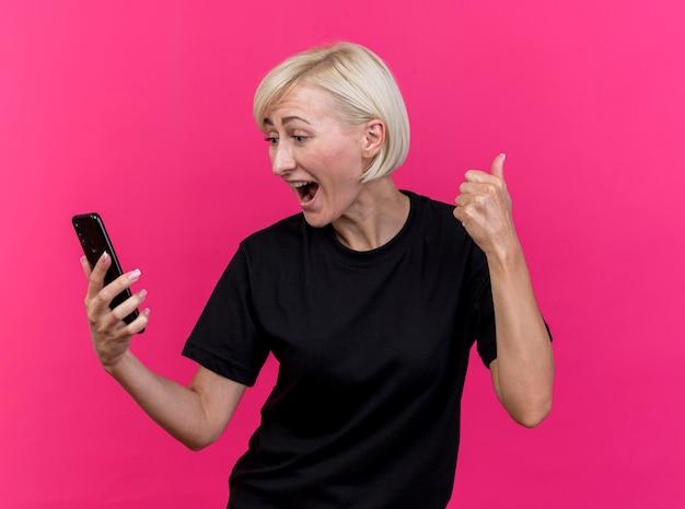 Blije blonde slavische vrouw die op middelbare leeftijd en mobiele telefoon houdt bekijkt die duim toont die omhoog op roze muur wordt geïsoleerd