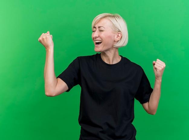 Blije blonde slavische vrouw die op middelbare leeftijd ja gebaar met gesloten ogen doet die op groene achtergrond wordt geïsoleerd