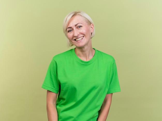Blije blonde slavische vrouw die op middelbare leeftijd voorzijde glimlachen bekijkt die op olijfgroene muur met exemplaarruimte wordt geïsoleerd