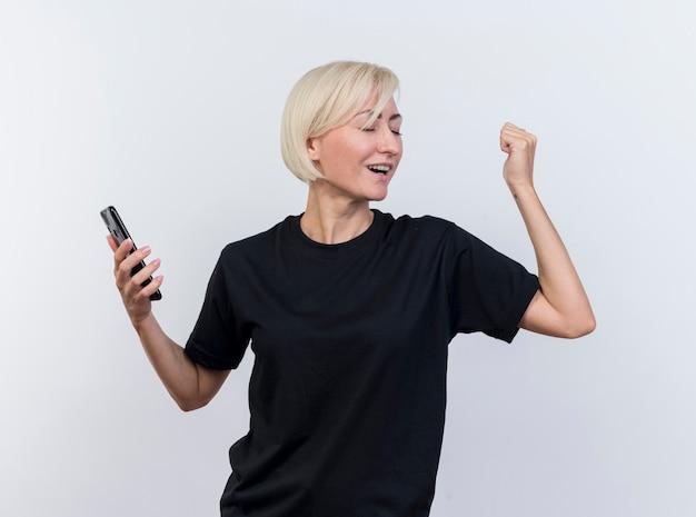 Blije blonde slavische vrouw die van middelbare leeftijd mobiele telefoon houdt die ja gebaar met gesloten ogen doet dat op witte achtergrond wordt geïsoleerd