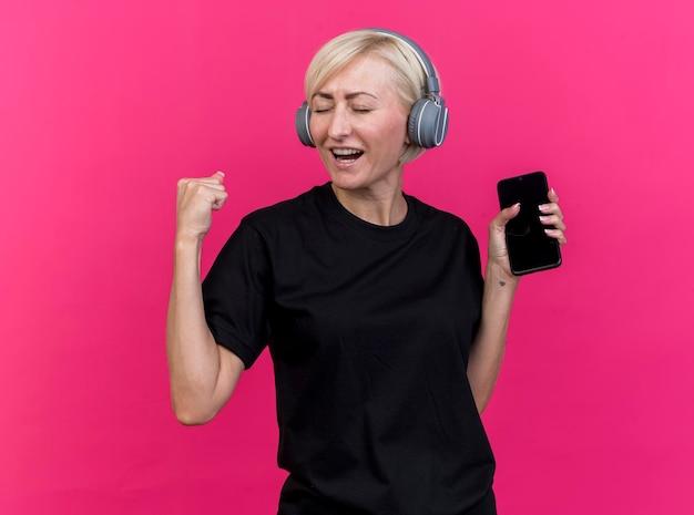 Blije blonde slavische vrouw op middelbare leeftijd die hoofdtelefoons draagt die mobiele telefoon houden die ja gebaar doen dat op roze muur wordt geïsoleerd