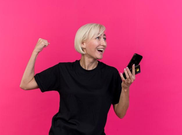 Blije blonde slavische vrouw van middelbare leeftijd die mobiele telefoon en creditcard houdt die naar kant kijkt die ja gebaar doet dat op karmozijnrode muur wordt geïsoleerd