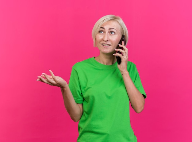 Blije blonde slavische vrouw van middelbare leeftijd die op telefoon spreekt die lege hand toont die kant bekijkt die op karmozijnrode achtergrond met exemplaarruimte wordt geïsoleerd