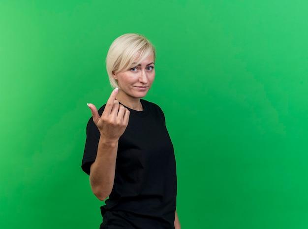 Blije blonde slavische vrouw van middelbare leeftijd die zich in profielmening bevindt die kom hier gebaar doet dat op groene muur met exemplaarruimte wordt geïsoleerd