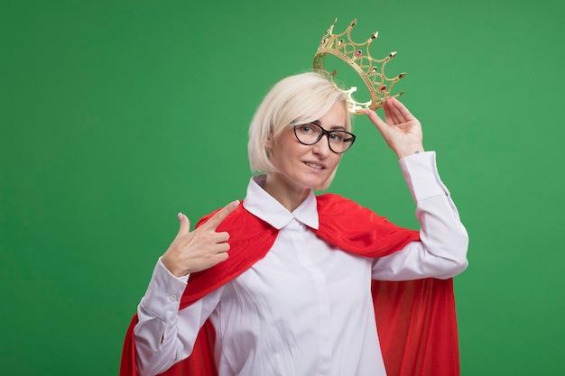 Blije blonde superheldenvrouw van middelbare leeftijd in rode cape met een bril die een kroon boven het hoofd houdt en naar zichzelf wijst