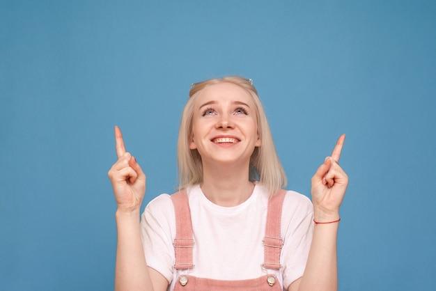 Blije blonde verschijnt vingers in een lege ruimte en glimlacht