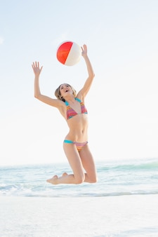 Blije blonde vrouw die een strandbal werpt