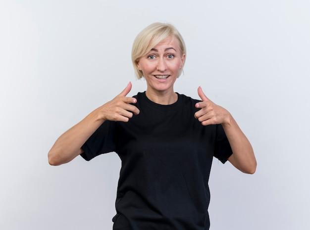Blije blonde vrouw die op middelbare leeftijd voorzijde bekijkt die duimen toont die omhoog op witte muur worden geïsoleerd