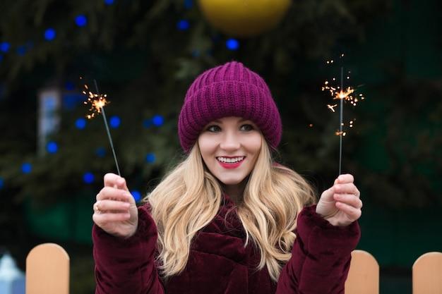 Blije blonde vrouw die plezier heeft met sprankelende bengaalse lichten op de nieuwjaarsspar in kiev