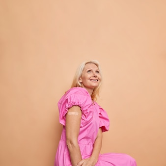 Blije blonde vrouw van middelbare leeftijd toont schouder met pleister nadat ze een vaccin heeft gekregen dat betrokken is bij immunisatie tegen de beige studiomuur van het coronavirus.