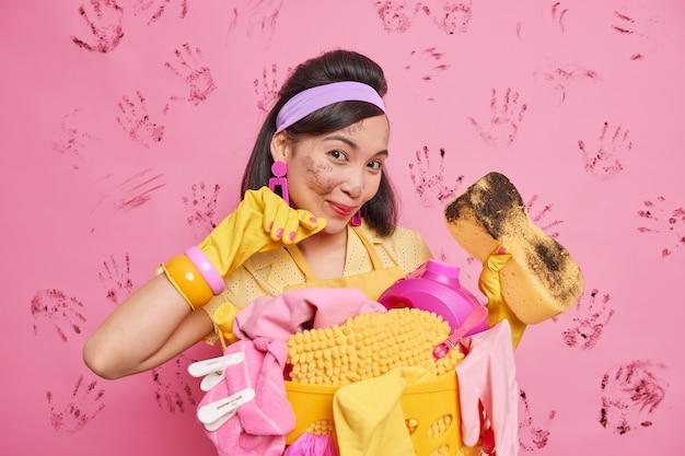 Blije brunette aziatische huisvrouw beschermt huis tegen vuil toont vuile spons na het afvegen van meubels draagt hoofdband latex handschoenen poseert in de buurt van wasmand gebruikt schoonmaakspullen heeft gezicht gevlekt