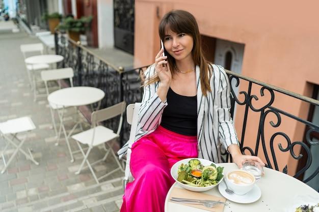 Blije brunette vrouw die koffie drinkt, smartphone gebruikt en geniet van het ontbijt in een stijlvol café op straat.