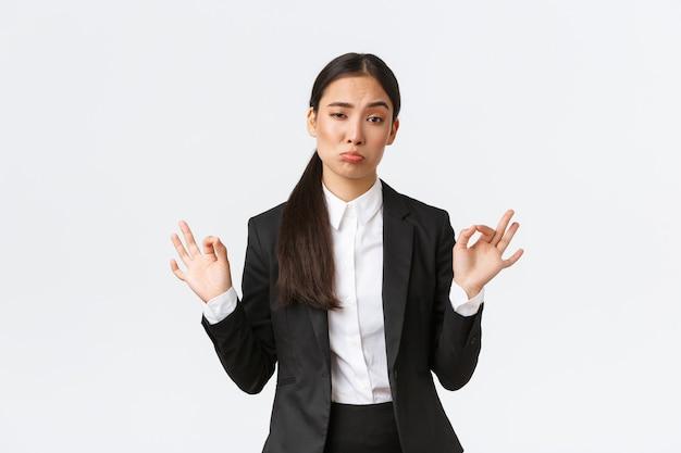Blije brutale aziatische zakenvrouw in zwart pak laat geen slecht gebaar zien, knik goedkeurend en maak oke...