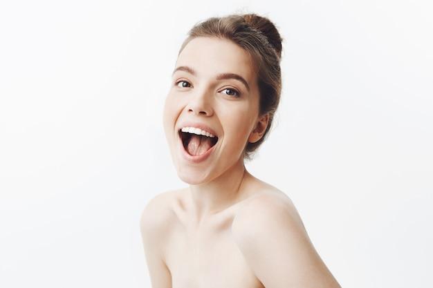 Blije charmante donkerharige europese jonge vrouw met knotjeskapsel dat helder glimlacht, lachend kijkt met opgewonden uitdrukking, poseert met blote schouders.