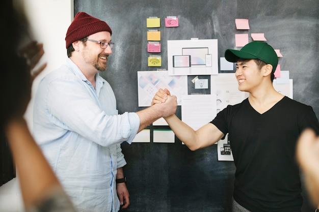 Blije collega's hand in hand op kantoor