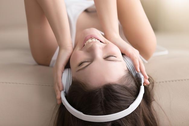 Blije dame die van populaire muziek in hoofdtelefoons geniet