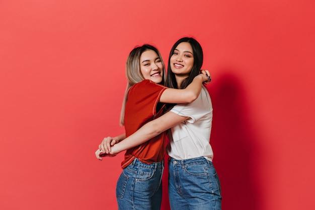 Blije dames in spijkerbroek knuffelen op rode muur