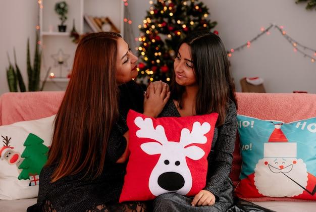 Blije dochter en moeder kijken elkaar aan terwijl ze op de bank zitten en genieten van de kersttijd thuis at