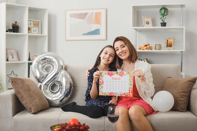 Blije dochter en moeder op gelukkige vrouwendag met kalender zittend op de bank in de woonkamer