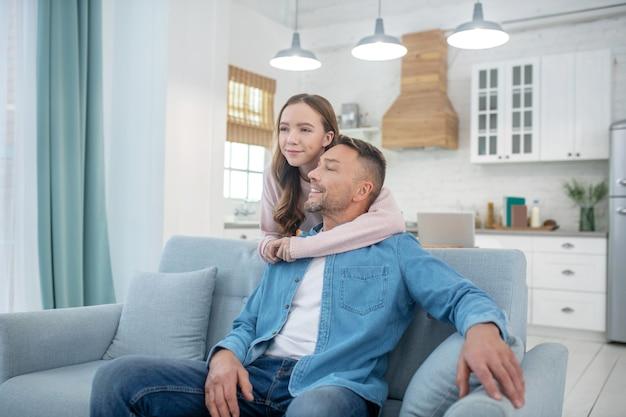Blije dochter is achter en knuffelt de nek van haar vader, die lacht zittend op de bank in de kamer.