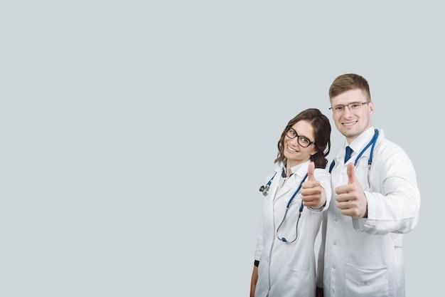 Blije doktoren. portret van twee artsen in witte jassen en glazen die duim op grijze geïsoleerde achtergrond tonen