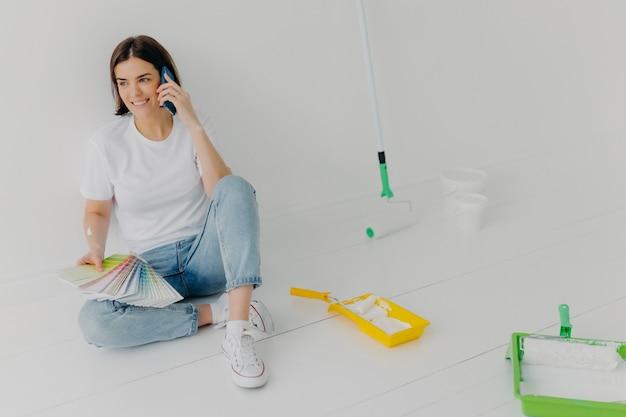 Blije donkerbruine vrouw die in vrijetijdskleding kleurensteekproeven houden