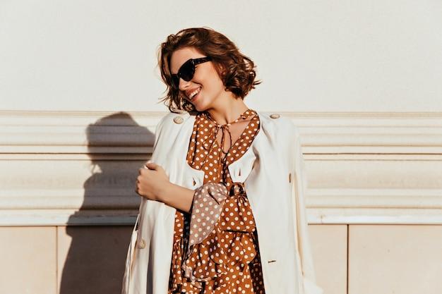 Blije donkerbruine vrouw die in witte laag dichtbij muur glimlacht. buiten schot van aantrekkelijke stijlvolle dame.