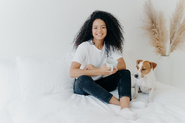 Blije donkere afro-amerikaanse vrouw voelt zich ontspannen, poseert in slaapkamer op comfortabel bed met rashond